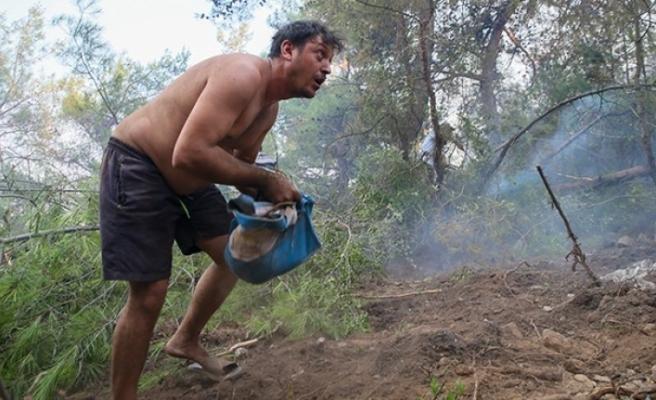 Orman yangınını söndürmek için kucak kucak toprak taşıdılar!